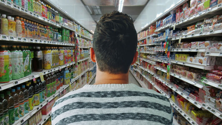 Back of man walking down a supermarket aisle