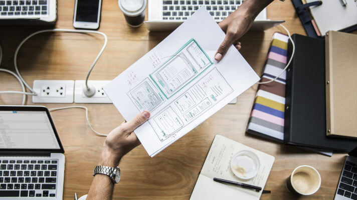 A blueprint is held by two people across a desk